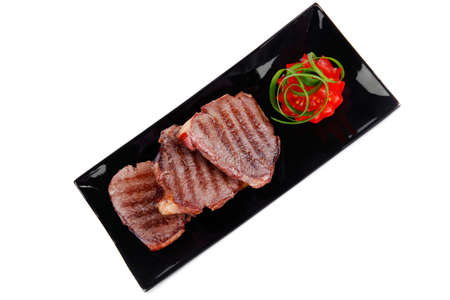roast meat beef fillet strips on black plate isolated over white background photo