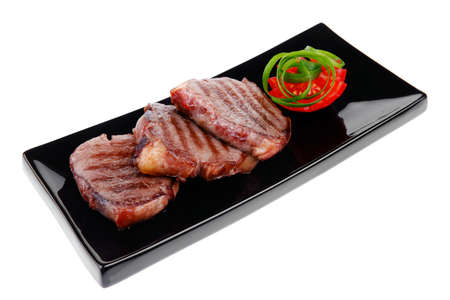 roasted beef meat steaks on black ceramic plate isolated over white  photo