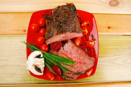 roasted meat served on red dish with vegetables photo