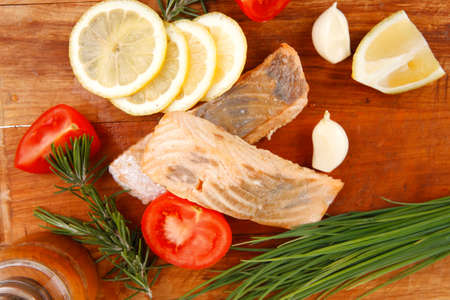 savory fish portion : grilled norwegian salmon fillet with green chinese onion, red cherry tomatoes , rosemary twigs and lemon slice on wooden board isolated over white  photo