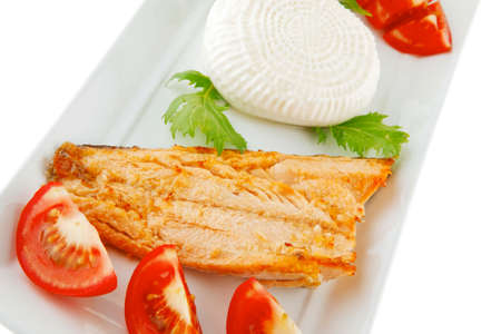 soft goat feta salt cheese with grilled sea salmon tomatoes and green lettuce salad served on white china plate isolated on white