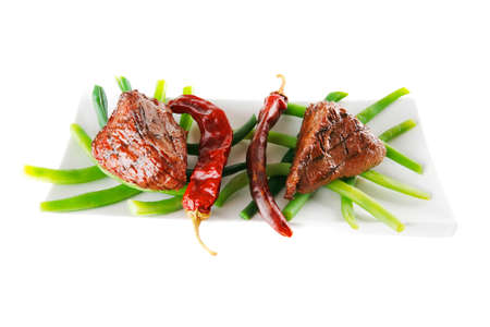 served grilled beef veal fillet entrecote on a white plate with peppers and green peas on long plate isolated on white  photo