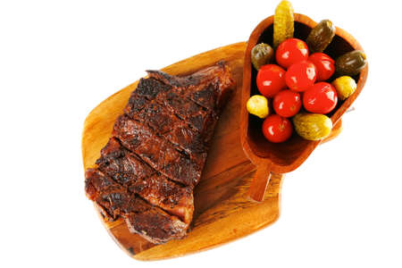 grilled steak entrecote and vegetables on wooden plate isolated over white