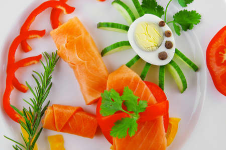 diet healthy food - smoked sea salmon rolls with vegetables and egg on plate isolated over white background photo