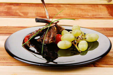 served ribs over wooden table with chives and grapes photo