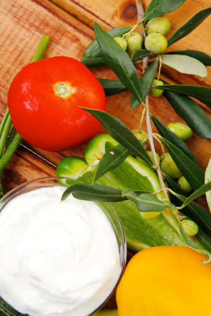 sour cream with vegetables over wooden table photo