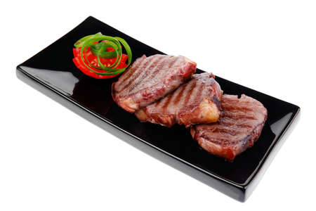 roasted beef meat steaks on black ceramic plate isolated over white background photo