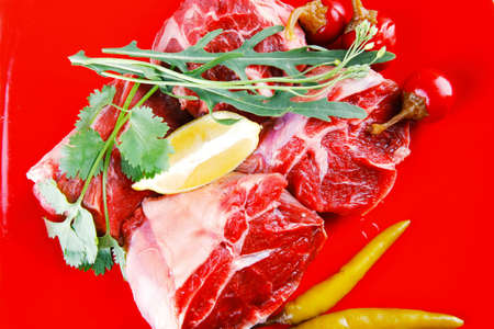 fresh raw beef red meat fillet medallion chunks on red plate isolated over white background photo