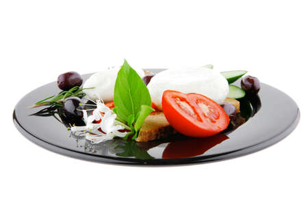 soft feta cheese on black plate with bread and vegetables photo