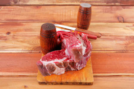 pepper castor: fresh raw uncooked beef fillet mignon entrecote on board prepared for cooking on wood table wtih cutlery and castors
