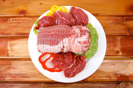 raw meat on plate over wooden table photo