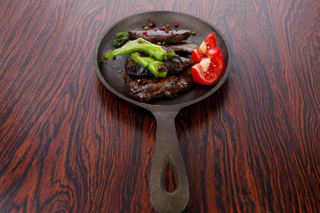 fresh roast beef fillet mignon on old retro style cast iron pan on retro wooden table as background with rosemary peppercorn and tomatoes photo