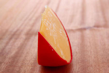 chunk of aged french cheddar cheese in hard red shell on wooden table photo