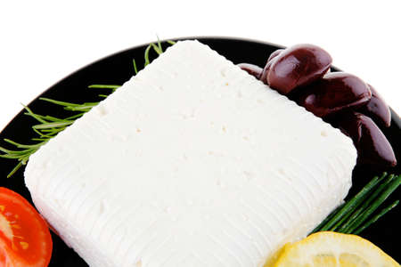 mediterranian: dairy food : image of feta cube on black plate isolated on white background Stock Photo