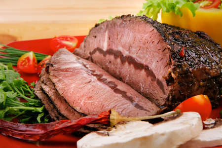 grilled beef sliced on red plate over wood photo