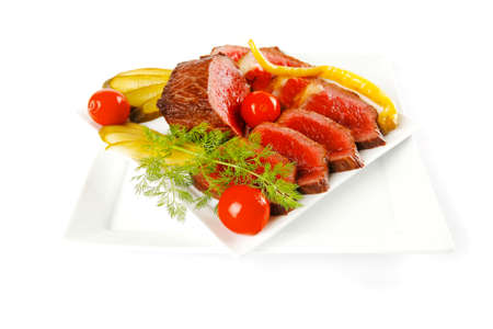 grilled beef meat entrecote on white plates with peppers and tomato isolated on white background photo