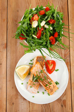 healthy sea food : roasted pink salmon fillet with vegetable salad on white dish over wooden table photo