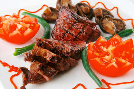 served grilled beef fillet mignon entrecote on a white plate with mushrooms and tomatoes on plate isolated on white background photo