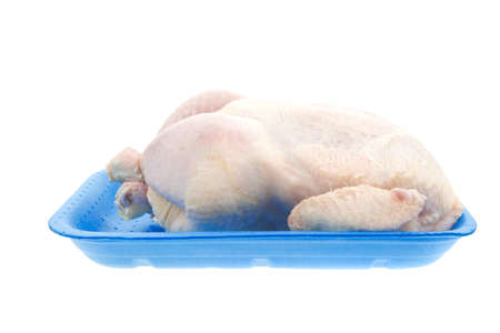 whole raw chicken on blue tray isolated on white background photo