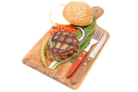 extra thick hot beef meat hamburger lunch on wooden plate with tomatoes and salad isolated on white background photo
