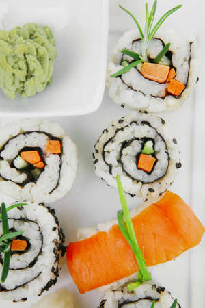 sake maki: Roll with Cucumber , Cream Cheese with raw Tuna and Salmon inside. on long white plate . Isolated over white background . Japanese traditional Cuisine