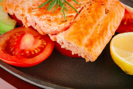 diet healthy food: hot grilled sea salmon fillet served on iron pan over wooden plate isolated on white background photo