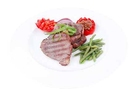 roasted beef meat strips steak on white ceramic plate with sweet pea and tomatoes isolated over white background photo
