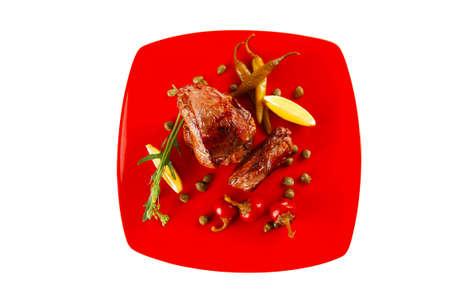 alcaparras: carne asada medallón de filete de carne con tomate cherry y pimientos picantes en la placa de color rojo aisladas sobre fondo blanco