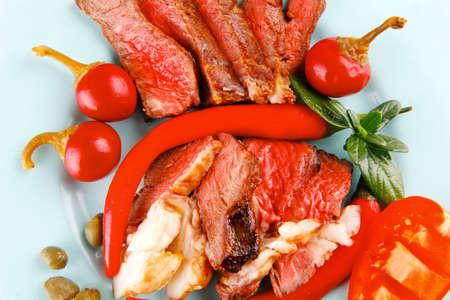 alcaparras: rebanadas de la carne el tocino servido con alcaparras de los tomates y Red Hot Chili Peppers en la placa azul sobre fondo blanco