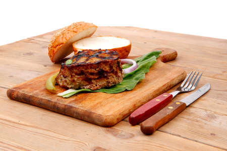 extra thick hot beef meat hamburger lunch on wooden plate with tomatoes and salad over wooden  table with cutlery and fresh sweet bun photo