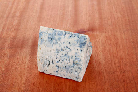 bit of aged french blue roquefort or cheese on wooden table photo