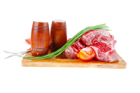 main course : fresh raw beef steak entrecote ready to prepare on cut board with green chives and tomatoes isolated on white background photo