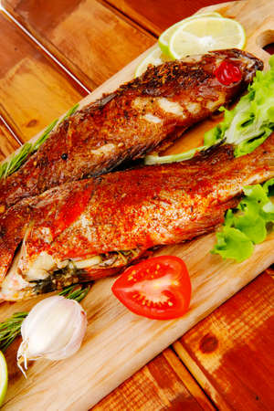 sunfish: healthy food: two fried sea bass fish served with tomatoes and vegetables on big wooden board over table Stock Photo