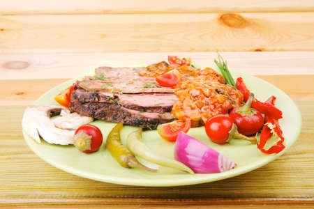 hot roast corned beef on green plate with red spiced tomato sauce over wooden table photo