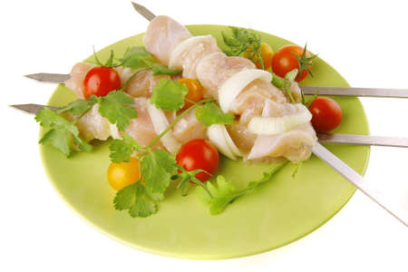 raw uncooked chicken shish kebabs with tomatoes on metal steel skewers on green plate isolated over white background photo