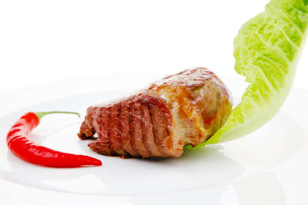 barbecued meat : beef ( lamb ) garnished with green lettuce and red chili hot pepper on white plate isolated over white background photo
