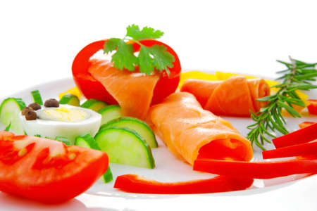 diet healthy food - fresh smoked sea salmon rolls with tomatoes egg and resemary on plate isolated over white background photo