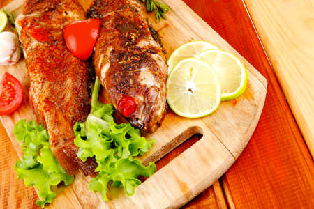 healthy food: two fried sea bass fish served with tomatoes and vegetables on big wooden board over table photo