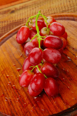 fresh raw red grape on wooden table photo