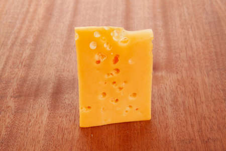 bit of aged french gold emmental or cheddar cheese on wooden table photo