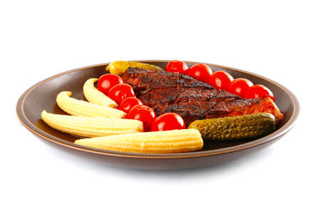 fresh red beef meat served with baby corns and cherry tomatoes on dark plate isolated on white background photo