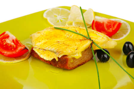roast sea sole fish fillet served on bread with tomatoes,olives and chives on green plate isolated over white background photo