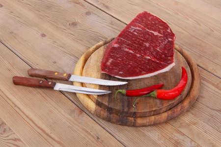 fresh raw beef meat steak chunk with red hot pepper on wood with stainless steel knife photo