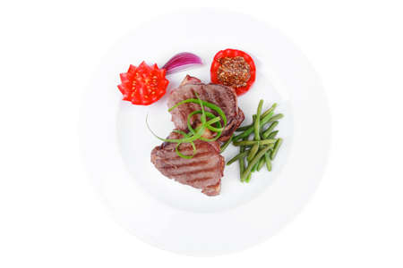 grilled meat beef steaks strips on white plate with sweet pea and tomatoes isolated over white background photo
