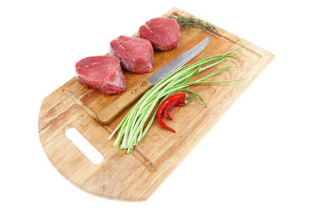 fresh meat : raw beef fillet on wooden board with thyme and red hot dry pepper ready to prepare . isolated over white background photo