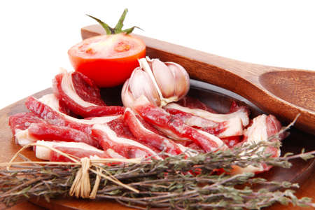 raw beef asado ribs with thyme and tomatoes on wooden board isolated over white background photo