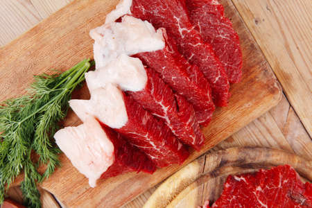 fresh raw beef meat steak and chunk with red hot pepper and dill on wooden cut plates over table photo