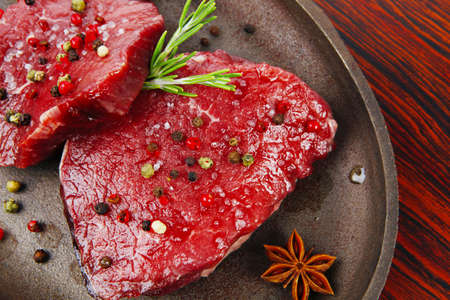 fresh raw beef fillet mignon on old retro style cast iron pan over retro wood table as background photo