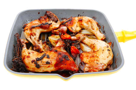 grilled chicken legs with tomatoes and thyme cooked on yellow ceramic pan isolated on white background photo