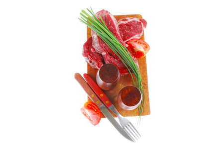 pepper castor: Fresh raw beef steak entrecote ready to prepare on cut board with green chives and tomatoes isolated on white  Stock Photo
